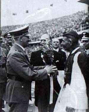هیتلر در مراسم گشایش بازی ها، شاخه زیتون را از قهرمان یونانی نخستین دور تازه المپیک ( 1896) دریافت می دارد