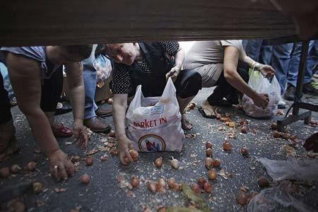 شهروندان یونانی در حال جمع اوری پیاز از کف خیابان در جریان اعتصاب فروشندگان خیابانی- آتن